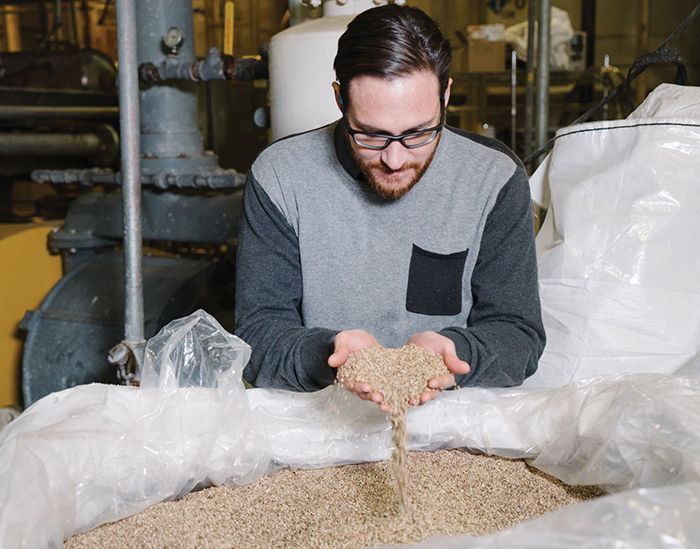 CEO/Founder Chad Rosen examines product derived from hemp seeds at the company's processing facility.